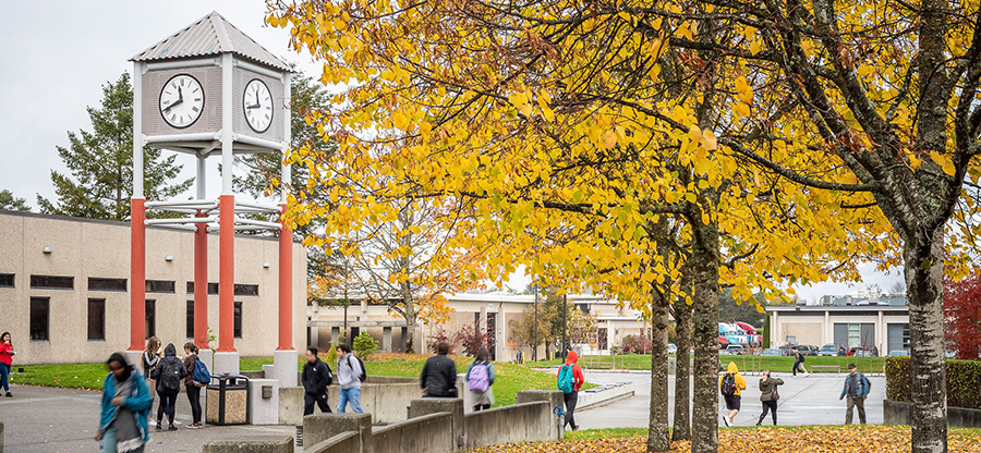South Seattle West Seattle campus clocktower and students walking gold leaves